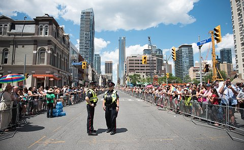 Two people in TPS uniform along a parade route lined with people