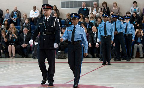 A woman in court officer uniform and a man in a dress uniform walk together.