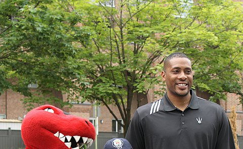 Raptors mascot, a woman in TPS uniform and a man on a basketball court