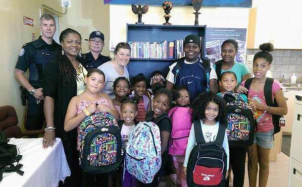 A group of men and women in TPS uniform, another woman with children holding backpacks