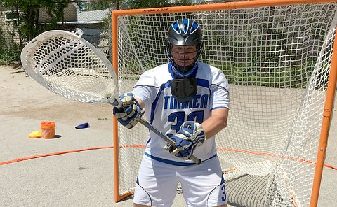 A man wearing a helmet holding a lacrosse stick in front of a net