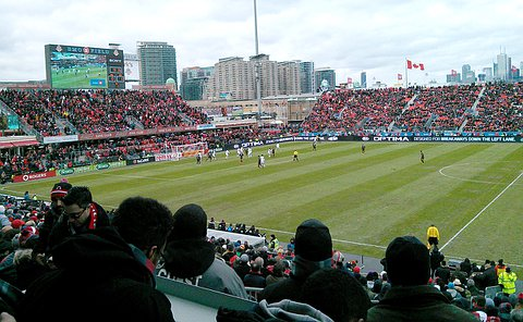 Soccer game in progress in a stadium with the Toronto skyline in background