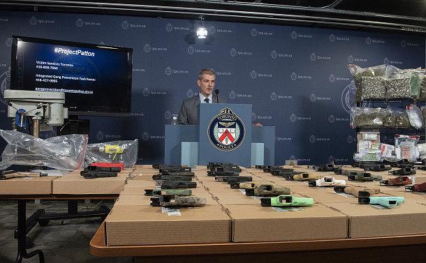 Man at a podium, table with guns, drill press