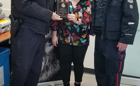 Two men in TPS uniform presenting plaque to woman