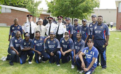 Three men in uniform with men in cricket uniform in several rows