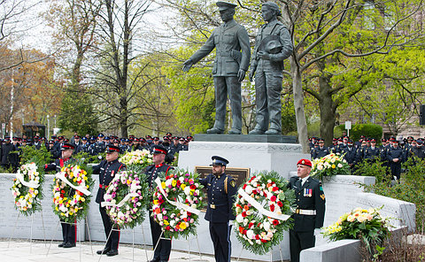 A group of men in police and military uniform behind wreaths