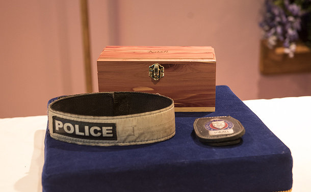 A wooden box, collar and TPS badge on a table
