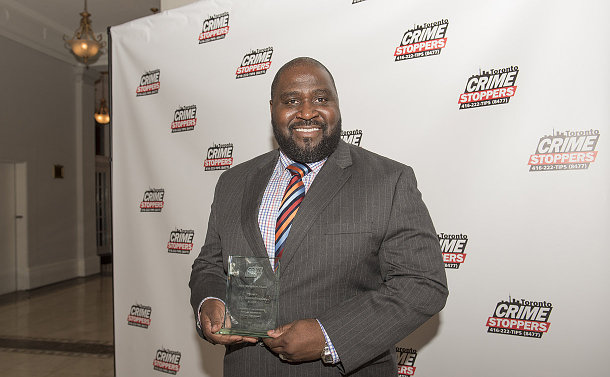 A man holding a glass award