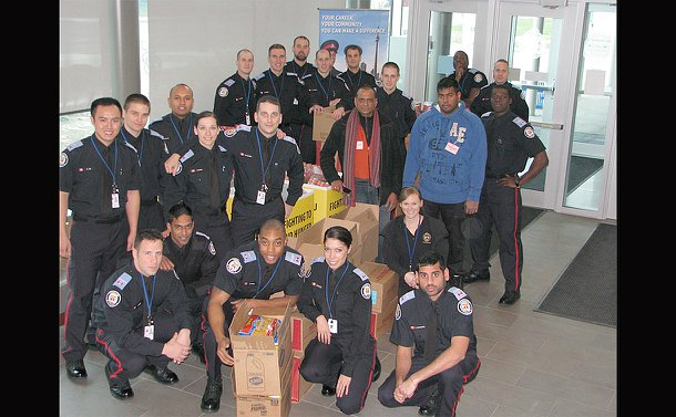 A group of men and women in TPS uniform with another man with boxes and holding food products