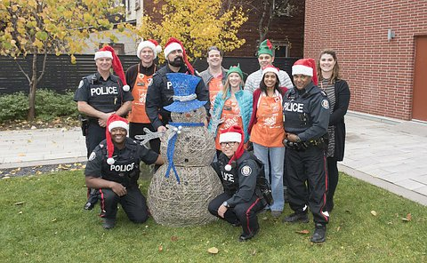 A group of men in TPS uniform wearing Santa hats with people wearing orange aprons