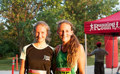 Two girls in running gear standing together smiling at the camera.