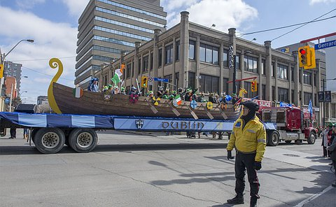 A man in TPS uniform looks at a float drive past