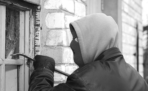 A man in a balaclava and hood uses a crowbar to break a window