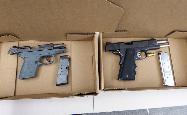 Two guns with clips out in boxes