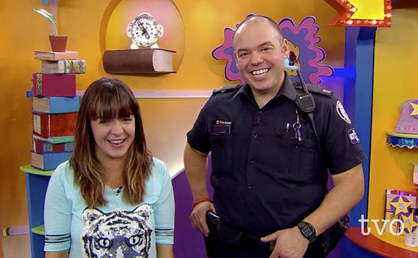 An officer on the set of a show with the host behind him. TVO logo on the bottom right corner