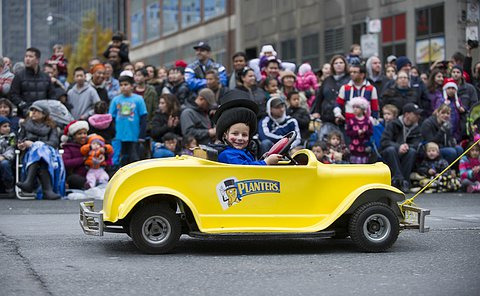 A boy sits in a toy car being towed by an adult