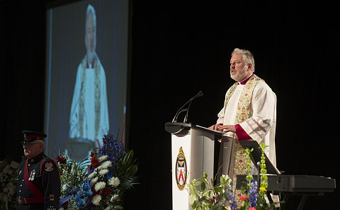 A man in a white robe and clerical collars speaks at a podium