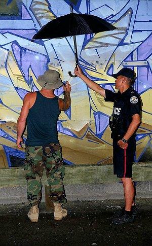 A man in TPS uniform holding an umbrella over a man spray painting a mural