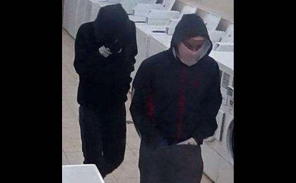 Two men in black hooded sweatshirts