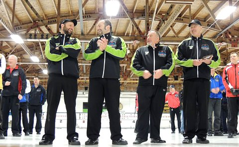 Four men stand together on curling rink in same uniform