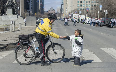 A man in TPS uniform on a bicycle reaches down to a boy holding out his hand