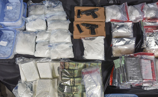 Powdered and crystallized substances with handguns on a table