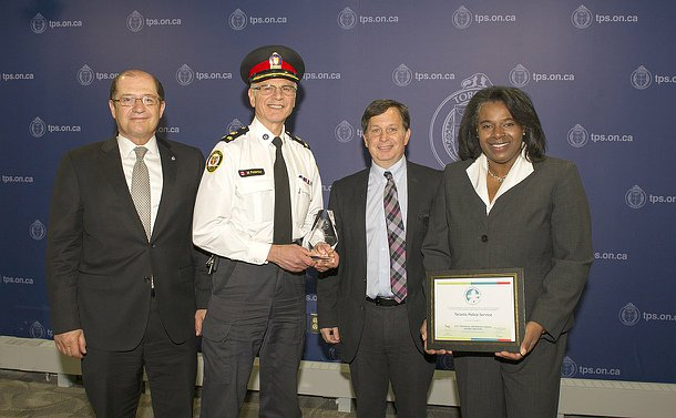 Three men and two women standing in a line, man in TPS uniform holding a glass award, woman holding a certificate