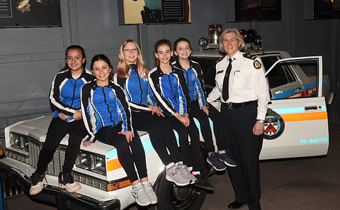 A group of girls with a woman in TPS uniform on a car