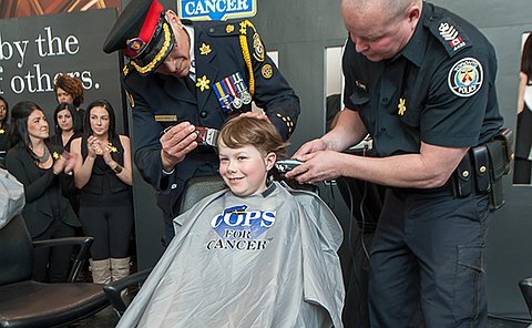 Two men in TPS uniform shave a boy's head