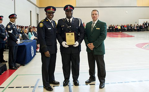 two men in uniform and one in a green blazer. Man in centre is holding a plaque.