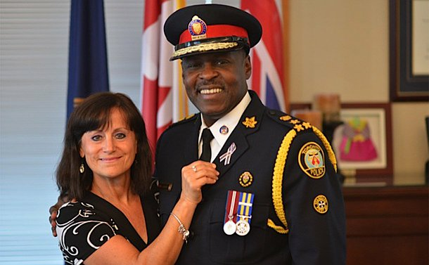 A woman stands beside a man in TPS uniform wearing a pink ribbon