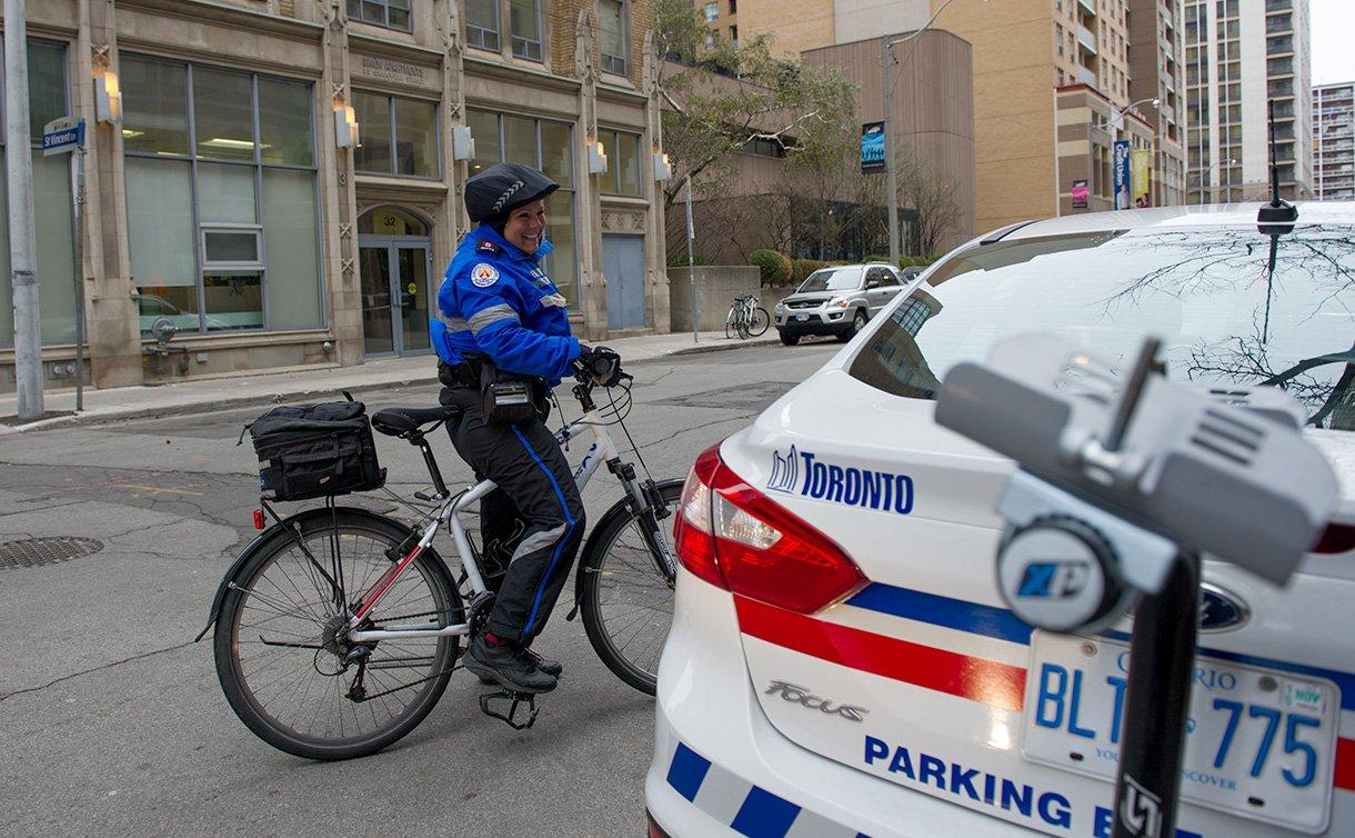 A woman in TPS parking uniform on a bike near a parking enforcement vehicle