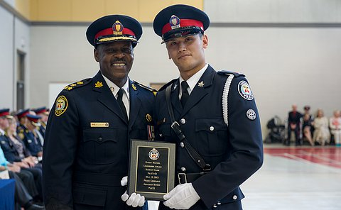 A constable standing with the Chief smiling, holding an award