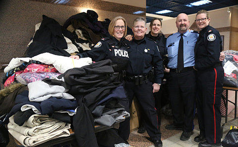 A group of people in TPS uniform in front of a pile of coats