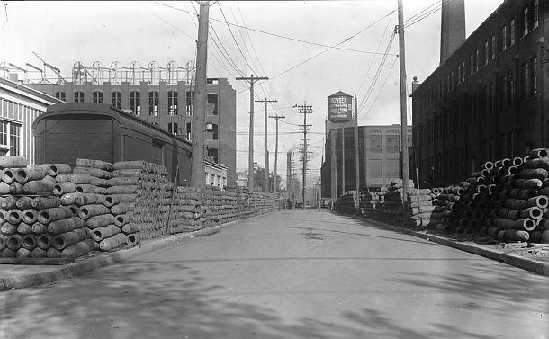 A street with factories and pile of shells on side