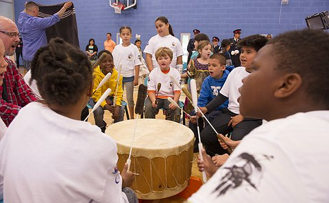 A group of children in white T-shirts seated and drumming in a circle