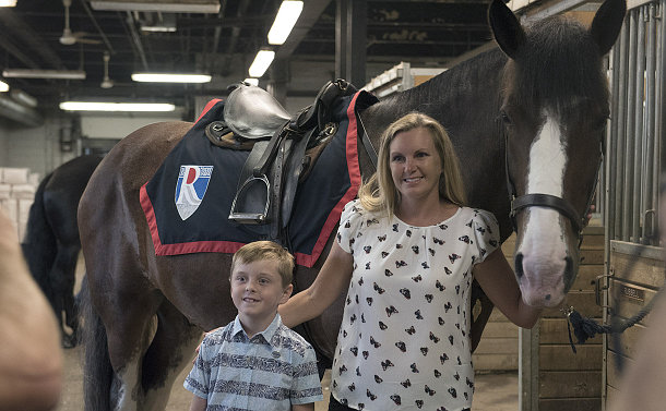 A woman and a young boy standing in front of a horse inside the stables
