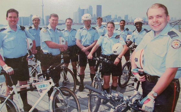 A group of men and women in TPS uniform holding bicycles with Toronto skyline in background