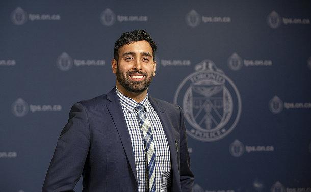 A man standing beside a TPS logo