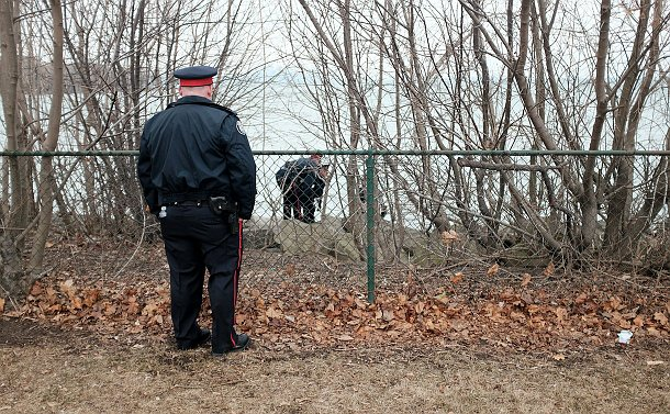 A fence, beyond it two officers looking down trying to help a man, in the foreground another officer standing guard, all outdoors by the lake