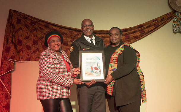A man with in TPS uniform with two women holding a certificate