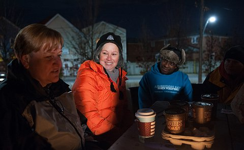 A woman speaks in the foreground as two people look at her. They are all dressed in outwear sitting around a bench, it is nighttime.