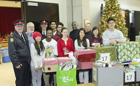 A group of people, including men in TPS uniform besides presents and a Christmas tree
