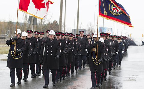 Three lines of men and women in uniform, some holding flags lead ahead of a larger group of officers