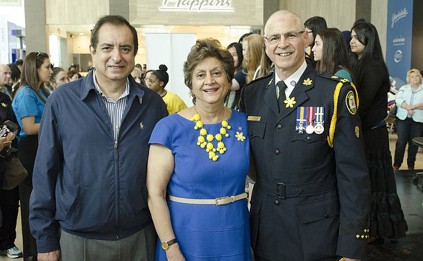 A man in TPS uniform with a man and a woman