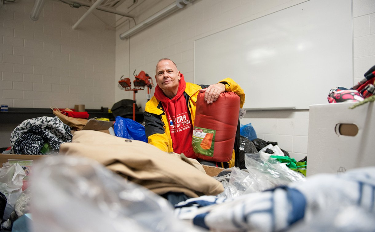 A man in a yellow jacket and red hoodie, sitting amongst an assortment of bags and boxes and sleeping bags, crouched on one knee looking at the camera.