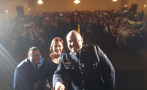 One man in TPS uniform with a man and woman in front of an audience