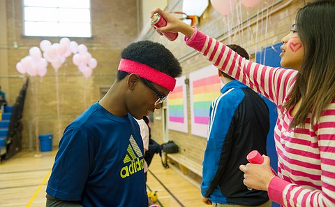 A girl spray painting the hair of a boy in a school gymnasium.