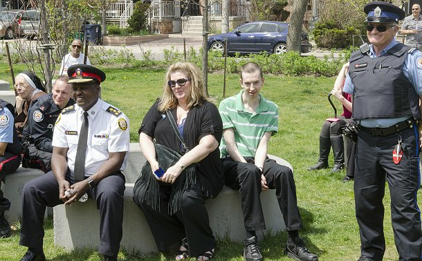 A man in TPS uniform sits among a group of people