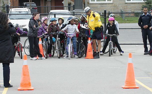 A man in TPS uniform points towards pylons beside a group of children on bikes as other adults look on